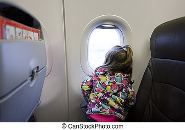Children and Infants air travel - Young girl looks out from...