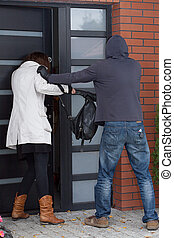 Break-in attempt - A robber attempting to break into a...