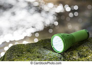 LED flashlight at waterside - LED flashlight on the mossy...