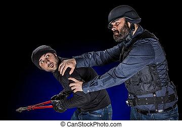 Arresting a Burglar - a cop wearing the SWAT tactical vest...
