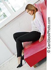 Woman on low red sofa from leather