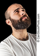 Desperation - a masculine bearded man isolated over a black...