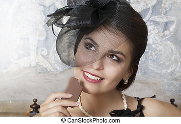 Pretty female eating a chocolate - Portrait of beauty young...