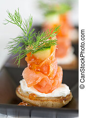 Blini with smoked salmon and sour cream, garnished with dill and caviar. Close-up view