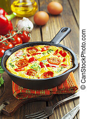 Omelet with vegetables and cheese. Frittata in a frying pan