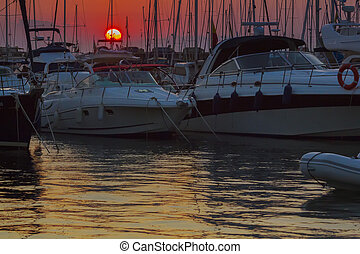 masts of sailboats at sunset