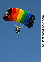 skydiver on a blue sky with rainbow parachute