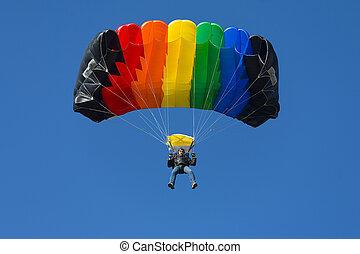 skydiver on a blue sky with rainbow parachute