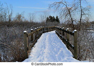 Adventure Ahead - A wood footbridge covered with snow in an...