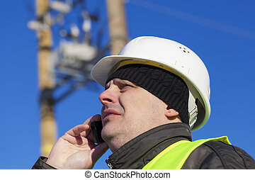 Electrical Engineer with cell phone near transformer