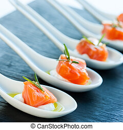 Smoked salmon delicatessen. - Numerous porcelain spoons with...