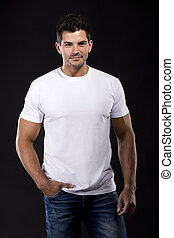 Handsome young man - Handsome latin man standing over a dark...