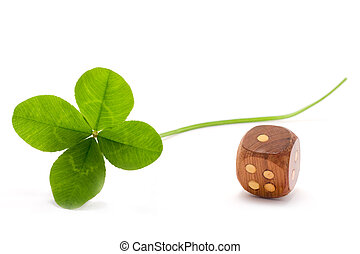 lucky clover and die - four leaves clover and wooden die on...