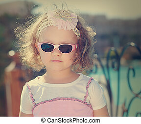 Beautiful kid girl in sunglasses on blue sea background....