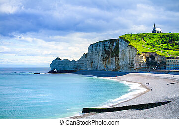 Etretat cliff and church landmark and its beach on morning. Normandy, France, Europe.