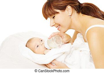Feeding Baby. Newborn eating milk from bottle.