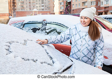 Beauty woman in the winter clothes with heart drawing on windshield of car