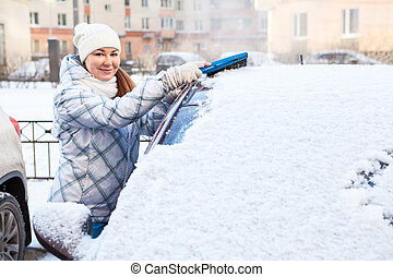 Attractive woman brushing snow from the car windshield