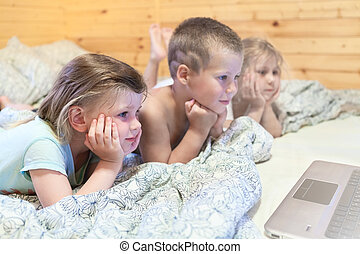 Lovely kids looking at computer monitor while laying in bed