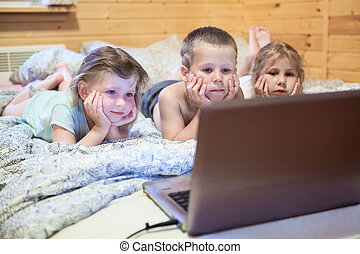 Pretty children looking at computer monitor while laying in...