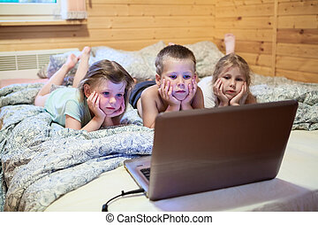 Three children looking at laptop monitor before sleeping in...