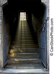 Staircase with light shining through window with metal bars