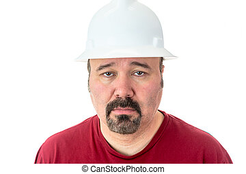 Morose glum looking man in a hardhat - Morose glum looking...