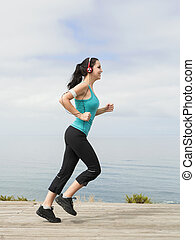 jogging - Beautiful young woman jogging on a boardwalk and...