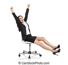 Happy business woman sitting on chair with arms up, isolated...