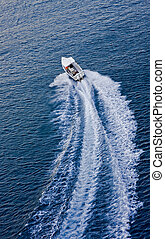 Boat Speeding Away - A white motorboat speeding away across...