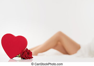 red heart and a rose in front of legs - red heart and a wet...