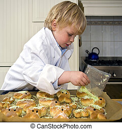 boy cooking - A small child decorating sweet bread with...