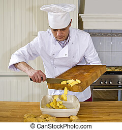 Preparing an ovendish - A chef shoving potatoes from his...