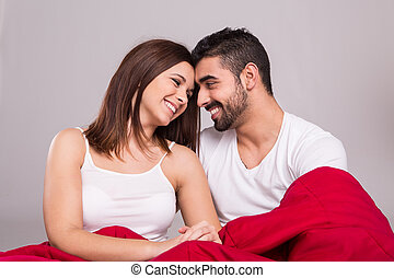 Couple in bed - Young love couple relaxing together in bed