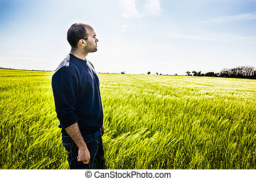 Looking away - a lone man walking in a big green field