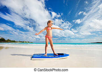 Little girl on vacation - Little girl practicing surfing...