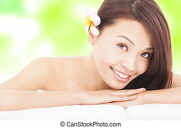 woman in spa club lying on the massage desk with towel