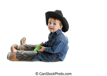 Toddler cowboy with dad\'s boots and squirt gun