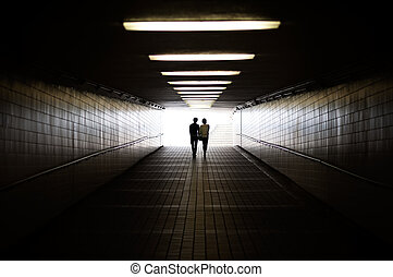 Young couple in silhouette walking towards exit of pedestrian underpass
