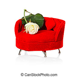 Red sofa, couch with white rose close-up isolated