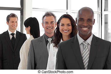 smiling Business man looking at camera with group in...