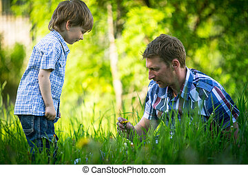 Father playing with his small son in the grass