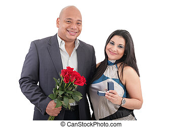 Couple holding ring and flowers isolated.  Anniversary and engagement concept.