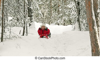 Extreme Sledding - Cheerful guy sledding down the slope in...