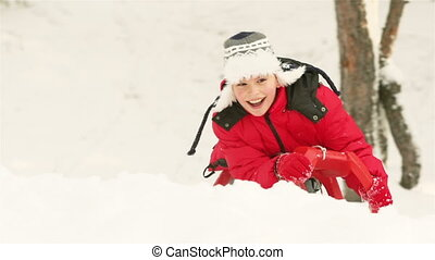 Winter Childhood - Smiling guy sledding cheerfully through...