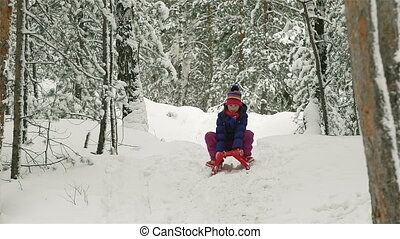 Wintertime Joy - Joyful cutie sledding in the winter woods
