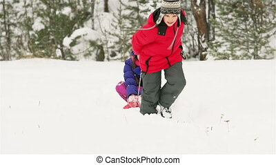 Sledding - Boy pulling the sled with his sister sitting on...