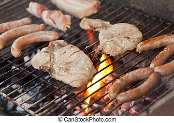 Flaming barbecue - Several type of meats being cooked on a...