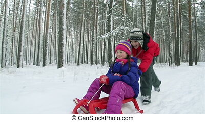 Winter Fun - Ecstatic kids having fun sledding on a snowy...