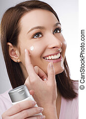 creme - young brunette woman applying creme on her face